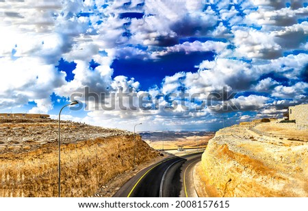 A road in a mountain canyon under a cloudy sky. Mountain road under sky clouds. Road in mountains in cloudy day