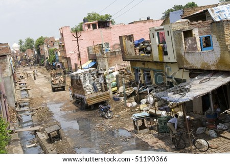 a road in an indian slum in agra, at the end of the road you see the dome of the monumental landmark Taj Mahal which symbolize the contrast of poverty and wealth.