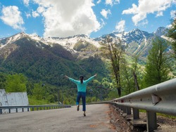 A road in the mountains. A young woman in a blue hoodie walks forward. Tourism and travel in the mountains.