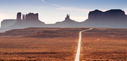 A road in the Utah desert with mountain plateaus, buttes in the background