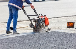 A road service worker compacts the asphalt on a fenced road section of the roadway with a petrol vibration plate compactor.