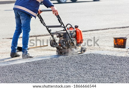 Photo of  A road service worker compacts the asphalt on a fenced road section of the roadway with a petrol vibration plate compactor.