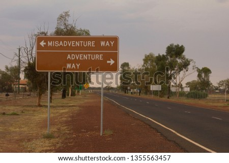 A road sign, changed to read Misadventure Way one way, adventure way the other, with an empty bitumen road running past #1355563457
