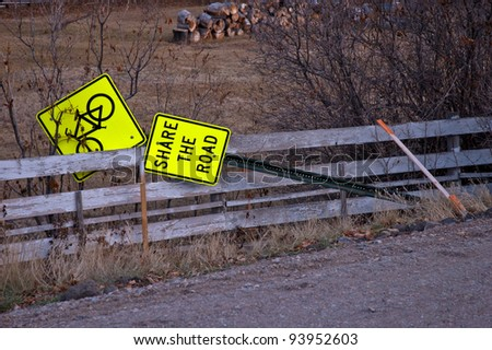 A road sign indicating the need to yield to bicycle traffic is seen lying against a fence near the shoulder of the roadway