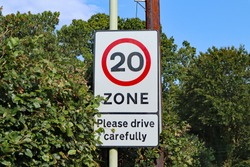 A road sign marking the start of a twenty miles per hour sign close to the village school