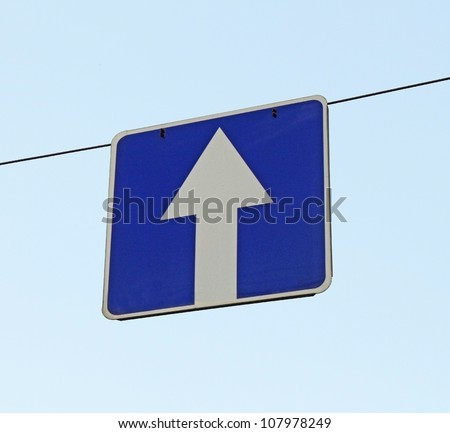 A road sign one-way traffic above the road