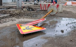 a road sign, stop, road repair is torn out of the ground and lies on a ruined city street against the background of people passing by
