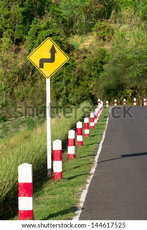 A road sign warns of a sharp turn on a narrow road