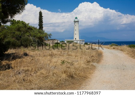 A road to lighthouse against clouds and blue sea  #1177968397