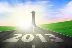 A road turning into an arrow rising upward with a road sign of success, symbolizing the direction to success in the year 2013