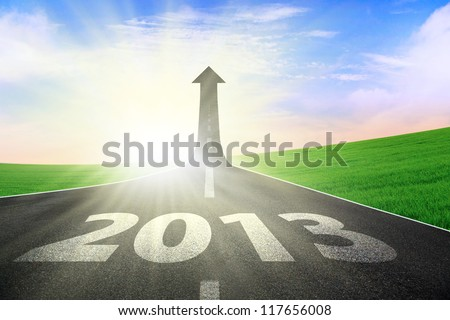 A road turning into an arrow rising upward with a road sign of success, symbolizing the direction to success in the year 2013 - stock photo