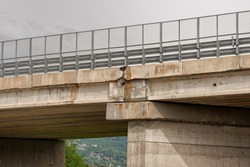 A road viaduct in reinforced concrete, with signs of corrosion. Concept of damage to infrastructure due to atmospheric agents