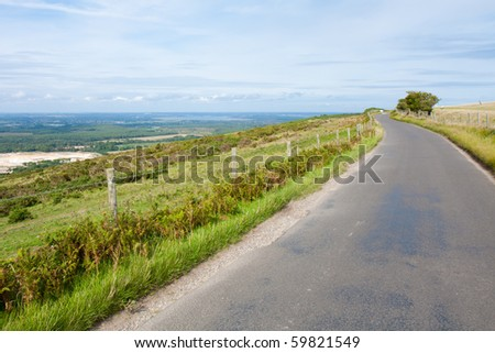A road winds around the edge of the top of a hill in England on a cloudy summer afternoon.