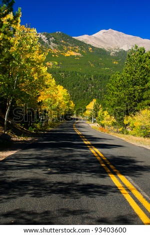 A road winds through the gold Aspen trees as the gorgeous blue Colorado sky and Rocky Mountains frame the scene