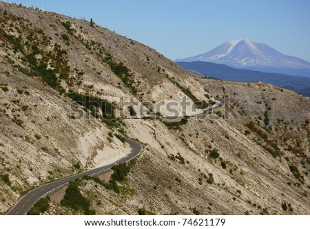 A road winds through the May 18, 1980 Mount St. Helens blast zone with Mount Adams looming in the background.
