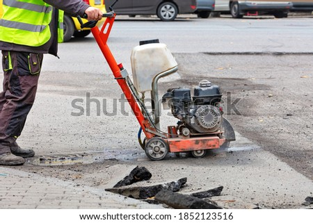 A road worker in reflective overalls uses a portable asphalt cutter to cut worn asphalt with a diamond blade to repair part of the roadway. Photo stock ©