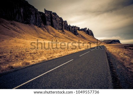 A road worthy of a trip leads along the mountainside, Iceland  #1049557736
