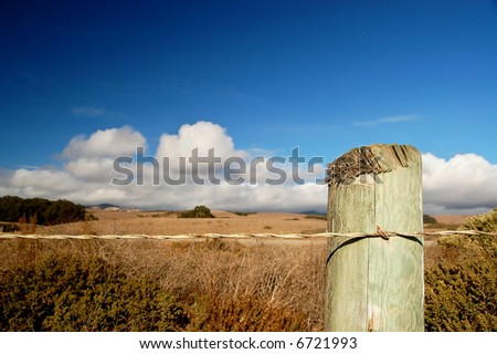 A roadside fence post under a blue sky along the Pacific Coastal Highway in California