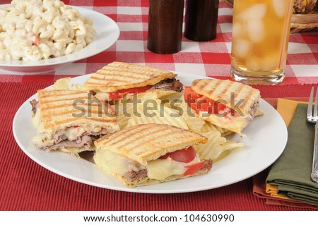 A roast beef panini with potato chips and macaroni salad