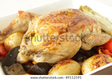 A roast chicken in a serving bowl on a bed of oven roasted vegetables, including potatoes, capsicum, endive, eggplant and garlic.