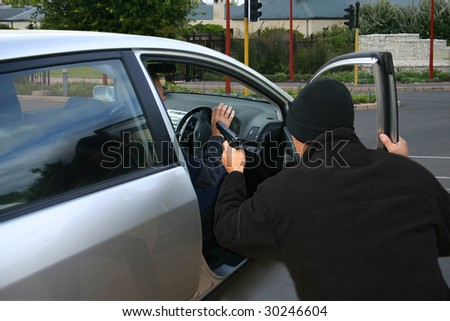A robber dressed in black pointing a gun at a driver in a car.