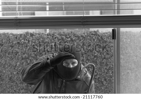 A robber peers through a window to see if anyone is home. - stock photo
