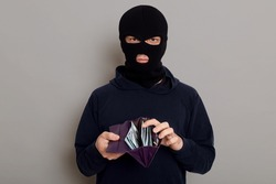 A robber thief man with a disguised face holds an open stolen wallet with money in his hands, looks at the camera, is dressed in a black hoodie, isolated on gray background.