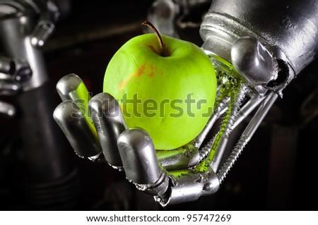 A robot hand holding a fresh apple closeup - stock photo