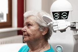 a robotic caregiver is combing the hair of a female senior adult, concepts like household nursing robot or helping technology in medicine