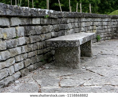 A robust stone bench placed against a stone brick wall.  #1158868882