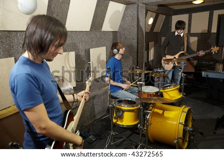 a rock band. two musicians with electrical guitars and one drummer working in studio