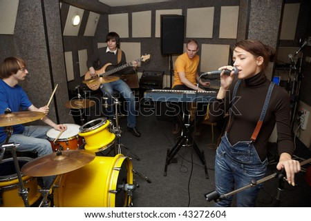 a rock band working in studio. vocalist girl is singing. focus on clothes of vocalist girl