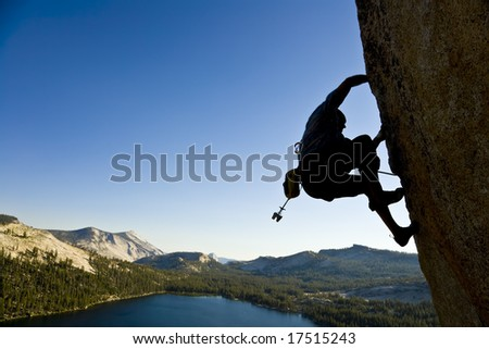 A rock climber desperately clinging to a rock face in Yosemite National Park, California, on a summer day.