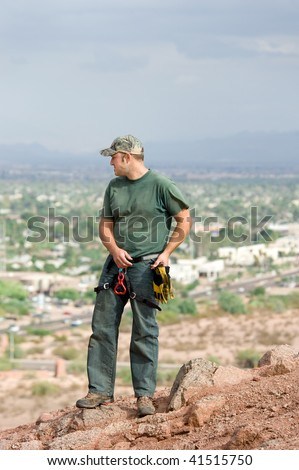 A rock climber examines the local environment before rappelling off the steep, highly elevated mountain top.