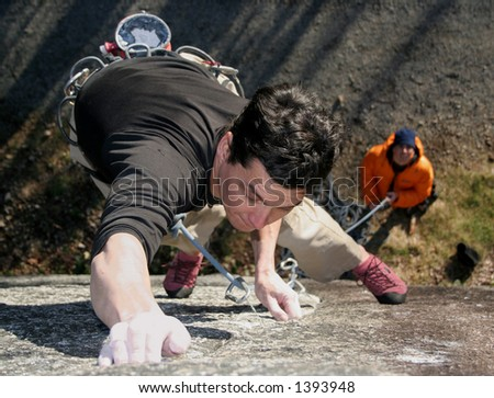 A rock climber struggles to hold on.