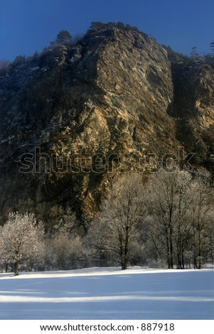 a rock face in the rising sun, snow-covered trees in the foreground.