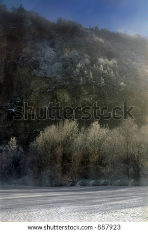 a rock face in the rising sun, snow-covered trees in the foreground. Slight fog enhances the atmosphere.