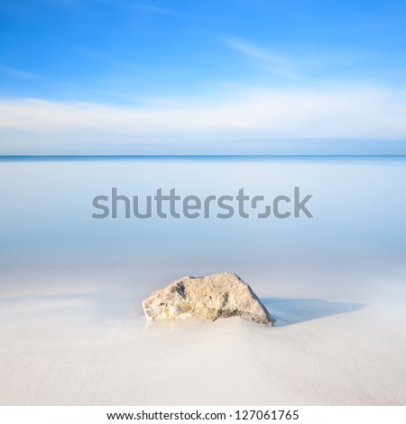 A rock on a white sand beach and blue ocean on horizon. Long exposure photography.