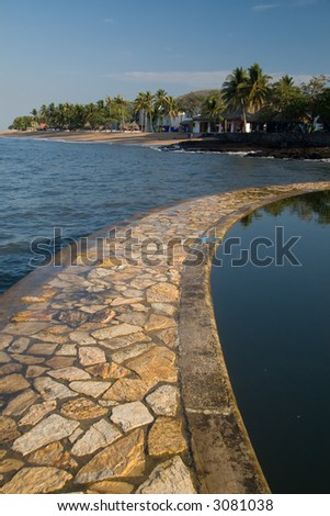 A rock path separates the sea from a salt water pool