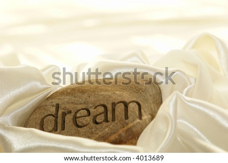 a rock with the word dream inscribed in it against a soft white satin background.