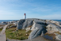 A rocky footpath among large rock boulders leading to a tall round vintage white tower lighthouse with a red watchtower at the top near the Atlantic Ocean. The background is a blue sky with clouds.