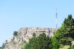 A rocky mountain peak with a flat plateau and antennas on it
