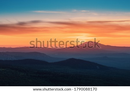 A rocky mountain range covered in the wild woods illuminated by the golden light of the setting sun. A natural Park reserve or hunting grounds. Recreational outdoor tourism Photo stock ©