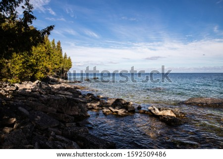 A rocky shoreline on Georgian Bay near Tobermory, Ontario as the sun shines down on it and the small waves hit the shore