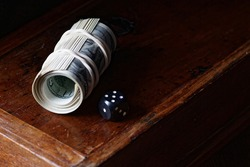 A roll of 100 american dollar banknotes with dice on wooden drawer on dark moody black background, closeup, copy space, finance and capital saving concept