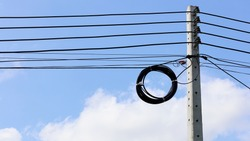 A roll of fiber-optic cables hanging from a pole. Optical fiber cable of high speed internet communication On a blue sky background and copy space. Close focus and select an object