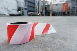 A roll of red and white Signal tape to safely fence off an area on the asphalt.