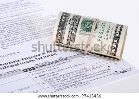 A roll of USD cash near an IRS tax form