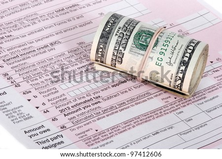 A roll of USD currency near an IRS tax form