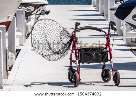 A rollator, also known as a wheeled walker and medical rolling walker, supporting a long-handled fishing net along a lakeside pier on a sunny day in summer #1504374092